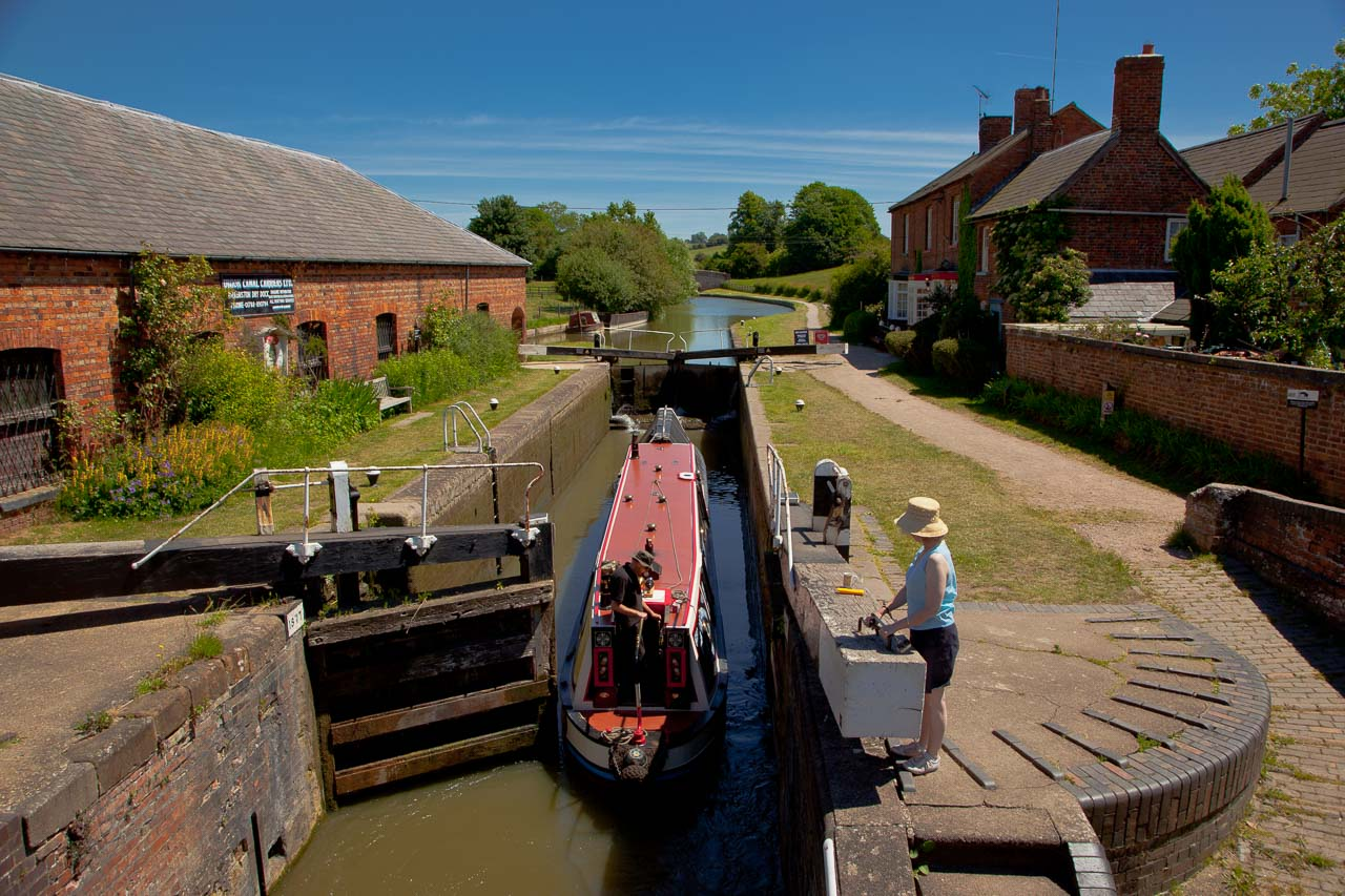 "Braunston Locks, on Grand Union looking over Lock 1. Photo taken on 22 June 2010 in superb Spring weather. This is a true canal and rural visually mixed experience. There are 6 locks in all set in rural surroundings but all close to the village. They lead up to Braunston Tunnel which can be ""legged"" if you want a purist experience, I'm told."